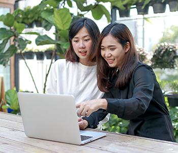 Deux femmes touchent l'écran de leur ordinateur
