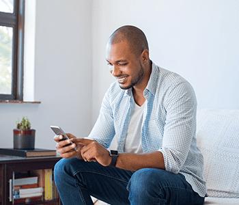 Homme souriant sur son téléphone