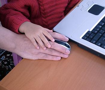 Un père guide son enfant à utiliser une souris d'ordinateur portable