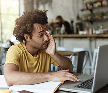 Un homme est fatigué à force de regarder son ordinateur
