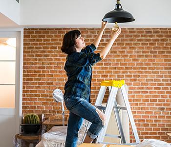 femme changeant une ampoule