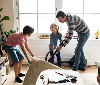 Une famille passe l'aspirateur sous le tapis