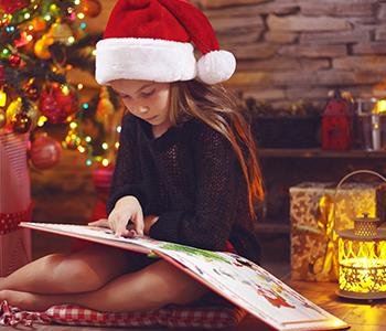 petite fille qui lit un livre à No¨el