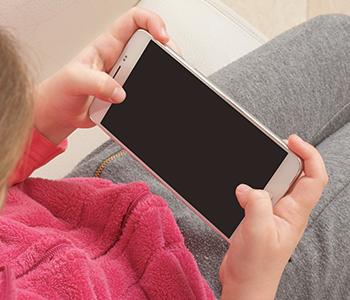 Une jeune fille joue sur son téléphone Android