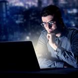 L'écran de son ordinateur illumine le visage d'un homme
