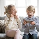 Un frère et une soeur jouent ensemble avec leur iPhone