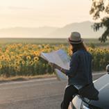 Assise sur le capot de sa voiture, une femme regarde une carte