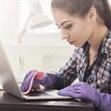 Jeune femme nettoie son ordinateur portable