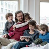 Papa sur un canapé entouré de ses enfants avec une tablette